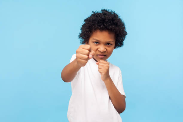 i'll knock out you! portrait of aggressive little boy with curly hair holding clenched fists up to attack - boy handcuffs stock pictures, royalty-free photos & images