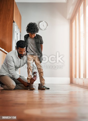 Shot of a man tying his little boy's shoelaces