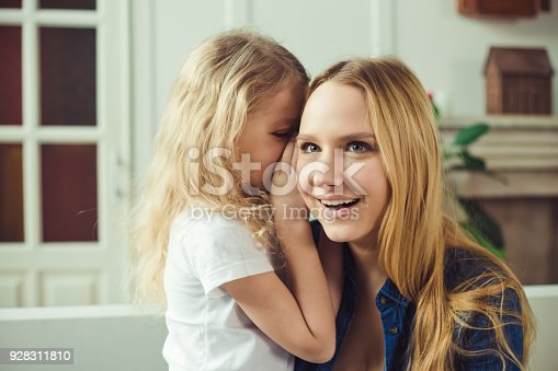 641288086 istock photo I'll tell you a secret. Cheerful smiling beautiful blond mother and daughter embrace sitting on the couch at home. Mothers Day. Women's Day. March 8. 928311810