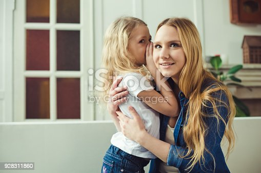 641288086 istock photo I'll tell you a secret. Cheerful smiling beautiful blond mother and daughter embrace sitting on the couch at home. Mothers Day. Women's Day. March 8. 928311860