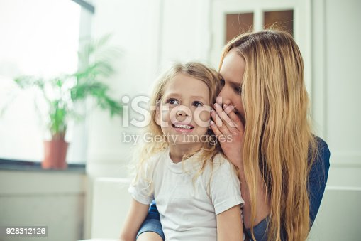 641288086 istock photo I'll tell you a secret. Cheerful smiling beautiful blond mother and daughter embrace sitting on the couch at home. Mothers Day. Women's Day. March 8. 928312126