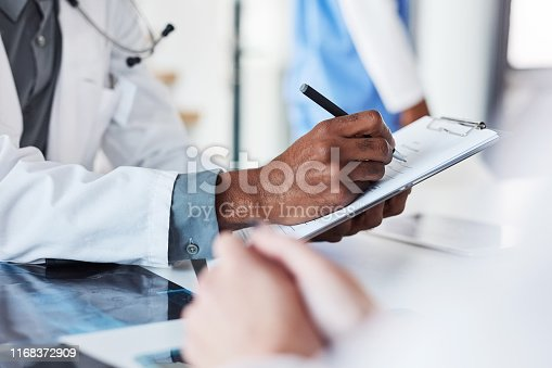 Closeup shot of an unrecognisable doctor writing on a clipboard in an hospital