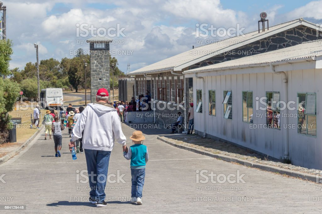 Llittle boy and grandfather visiting the maximum security prison on Robben Island, where Nelson Mandela was imprisoned - Illustrative editorial image stock photo