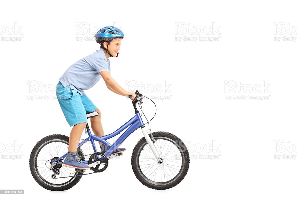 Llittle boy with blue helmet riding a small blue bike stock photo