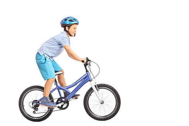 Llittle boy with blue helmet riding a small blue bike stock photo