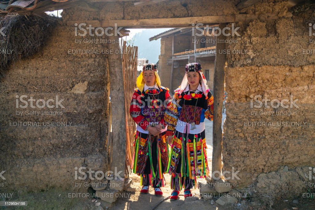 Lo Lo ethnic minority woman in traditional costume with old wall-thicked house at Lo Lo Chai village, Dong Van district stock photo