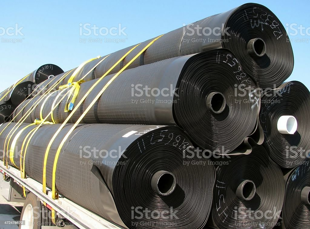 Load of black insulation rubber material rolls stock photo