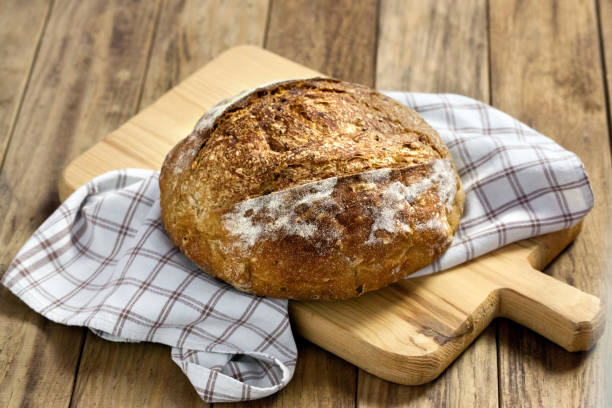 Load of bread on cutting board Load of bread with napkin on wooden cutting board round loaf stock pictures, royalty-free photos & images