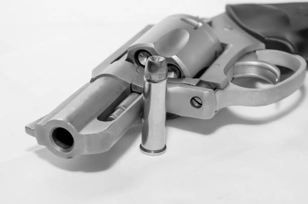 A loaded 357 stainless steel revolver with a hollow point bullet next to it stock photo