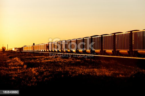 The setting sun glints off a trainload of coal wagons/hoppers giving the train a golden glow.  The wagons are loaded with coal for domestic power generation. .  In the distance, a stack train approaches.  Horizontal, Copy Space.