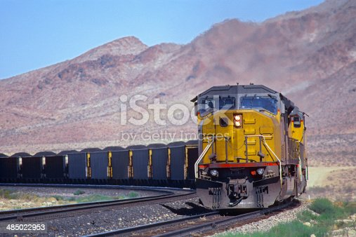 Two powerful diesel locomotives round a corner with a heavily loaded coal train.  In the background are rugged hills.  Logos and ID removed.  Horizontal, copy space.