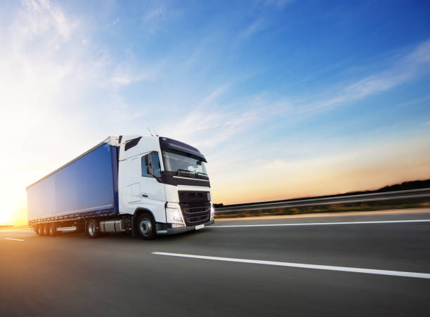 Loaded European truck on motorway in sunset stock photo