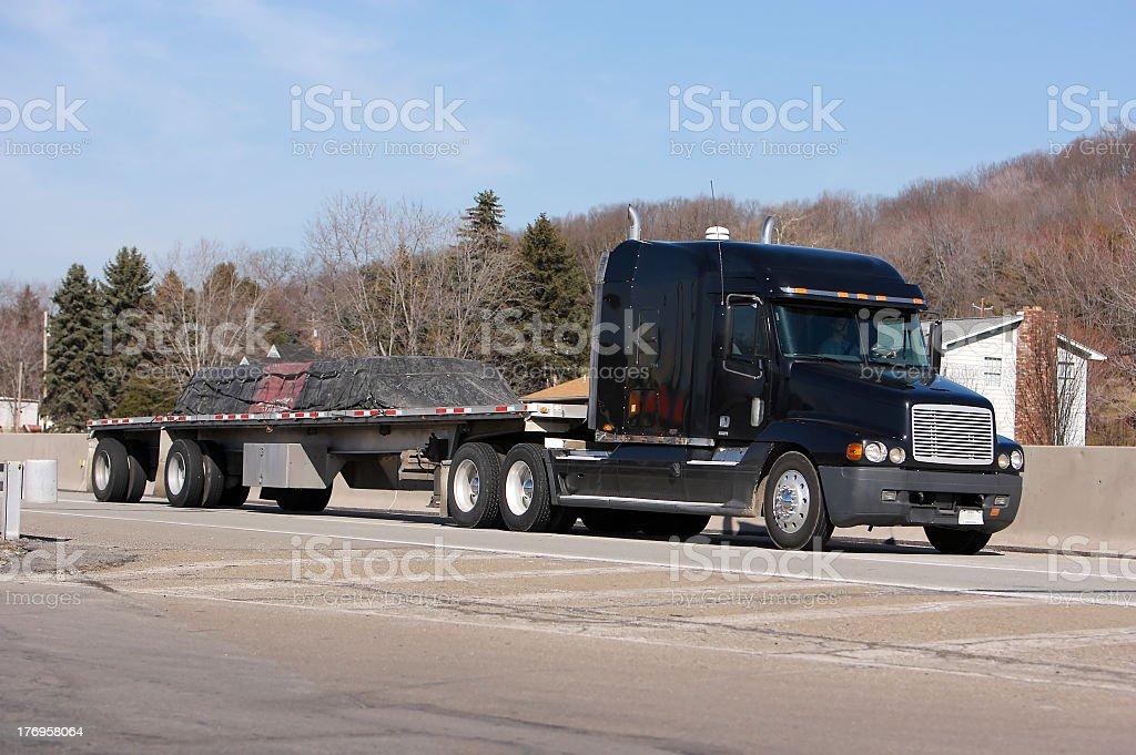 Loaded Flatbed black semi truck royalty-free stock photo