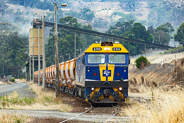 Loaded Hanson stone train waiting to depart Kilmore quarry Kilmore East, Australia - January 21, 2016: The drivers on diesel locomotive G512 chat prior to departing the Hanson stone quarry at Kilmore East with a train-load of aggregates for the building and construction industry.  QUBE Logistics Rail Services took over operating the service from Pacific National in January 2016. depart stock pictures, royalty-free photos & images