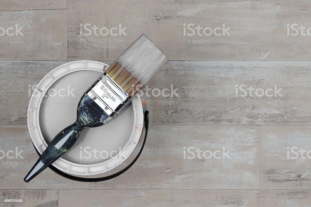 Loaded paintbrush placed across an open can of grey paint stock photo