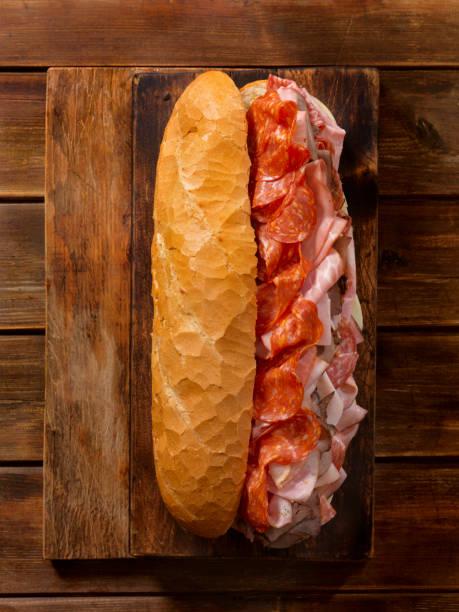geladene partei sub sandwich auf ein stangenbrot - roast beef sandwich stock-fotos und bilder
