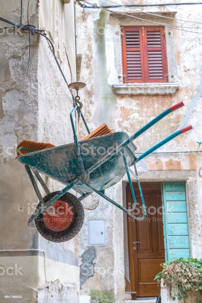 Loaded wheelbarrow at construction works in an ancient street. royalty-free stock photo