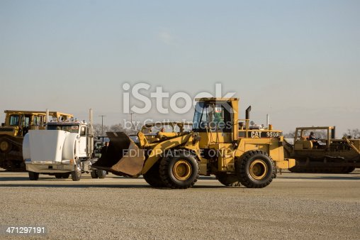 Tipton, CA, USA - February, 11 2011: An auction worker drives a CAT 950F loader away from the auction ring. It has just been sold at a no reserve auction at the Ritchie Brothers auction yard.