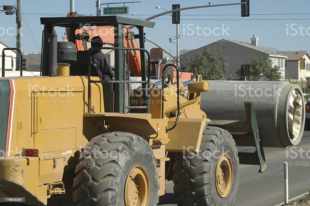 Loader carrying cement pipe royalty-free stock photo