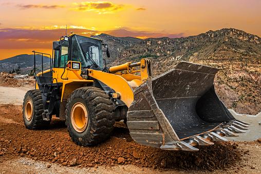 Loader Excavator at  Construction site at sunset