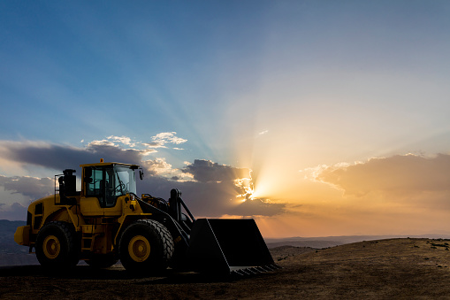 Loader Excavator working at sunset