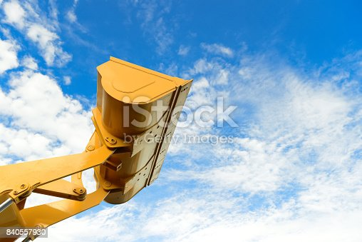 loader part of the backhoe loader tractor machine in yellow color with blue sky in background.backhoe loader while working in industry