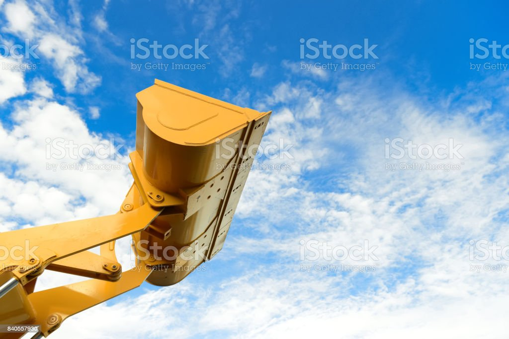 loader part of the backhoe loader tractor machine in yellow color with blue sky in background.backhoe loader while working in industry stock photo