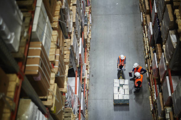 Loaders at work Group of workers in uniform and helmets having talk in aisle warehouse interior stock pictures, royalty-free photos & images