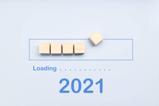 Loading 2021 year on wooden cubes on a blue background. Downloading new year 2021 stock photo