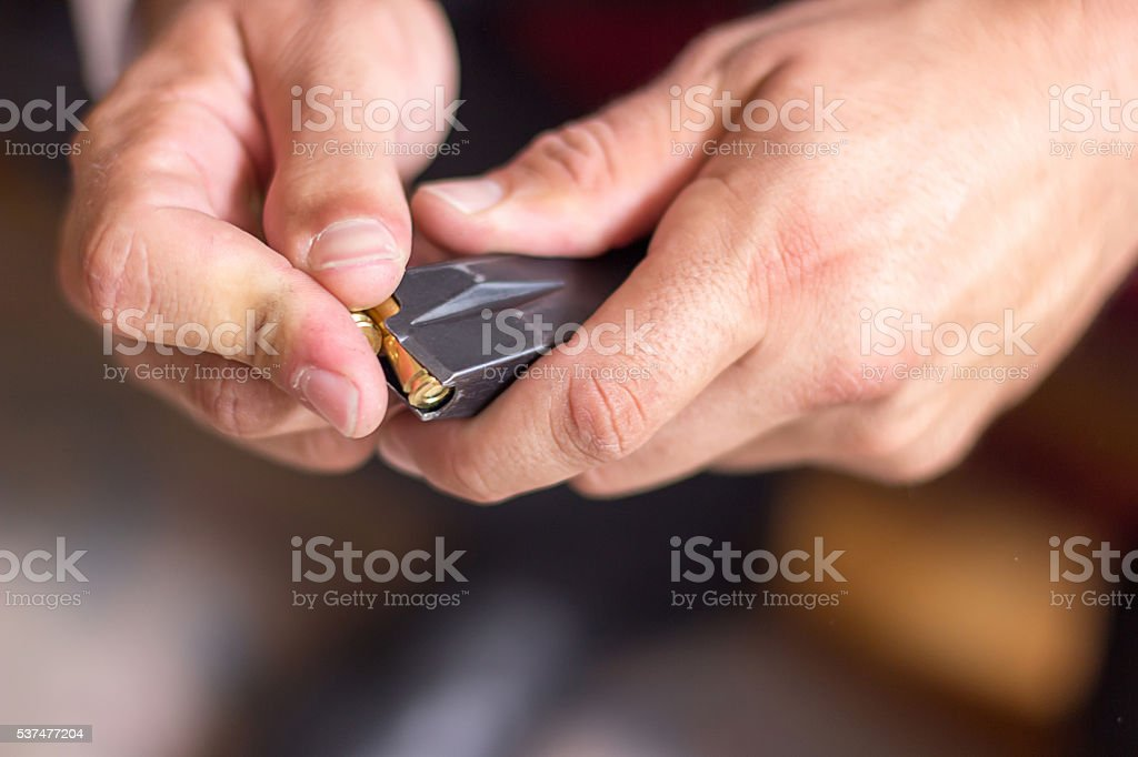 Loading a magazine, Loading Gun, Preparing for crime. stock photo