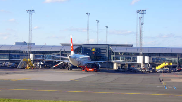 Loading airplane parked by Copenhagen airport building, stairs and luggage carriers nearby stock photo
