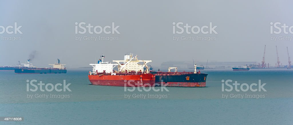 Loading anchored oil supertanker via a ship-to-ship oil transfer stock photo