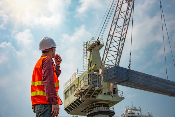 Loading at risk worker stevedore or foreman, engineering, loading master talks to crane driver by walkie talkie for safety lifting the goods shipment, lifting by gantry crane, working at risk on the high level insurance hooikoorts stock pictures, royalty-free photos & images