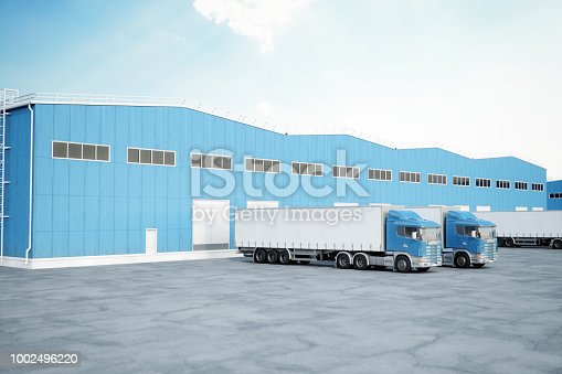 Modern loading bay with overhead doors and trucks. Copy space on truck's container.