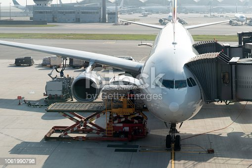 186763256istockphoto Loading cargo on plane in airport before flight. Foreman control loading Containers box to cargo plane. 1061990798