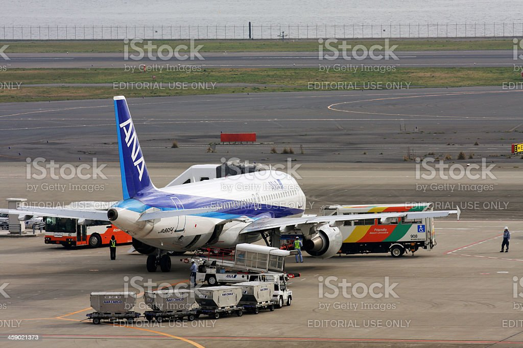 Loading cargo to ANA Airbus A320-200 jet airplane royalty-free stock photo
