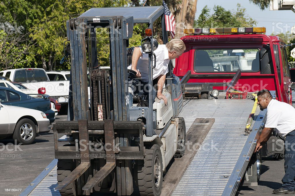 Loading Forklift onto a Tow Truck stock photo