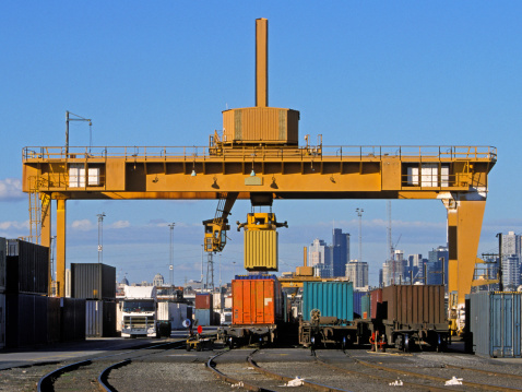 A large straddle crane loads freight containers from trucks to trains at a city intermodal hub.  High-rise buildings loom in the background.  A yellow container is in transit.  Three lines of rail wagons are being loaded with containers aa a fourth line is empty.  Trucks and stacks of containers complete the picture. Copyspace.