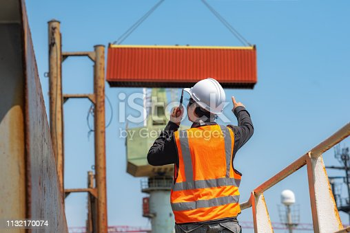 foreman, supervisor, port controller, loading master in charge of works at job site, control to the teamwork by walkie talkie radio for job done in the same direction, working at risk and high level of insurance