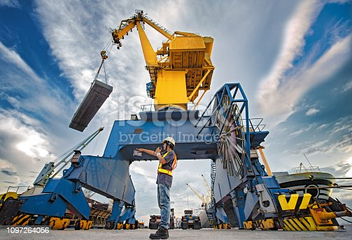 stevedore foreman and or supervisor, loading master takes control in loading discharging operation by walkie talkie and device on line, port operation working under control at quayside