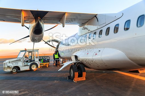 istock Loading luggage in airplane at daybreak 618340280