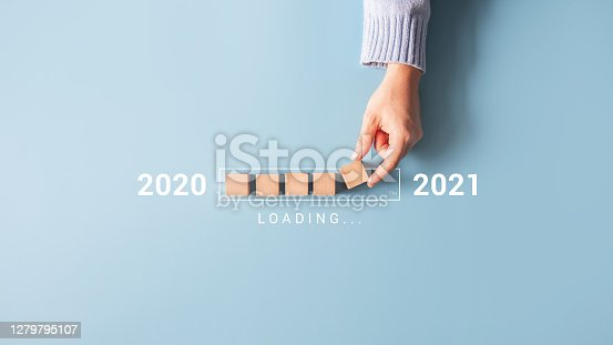 istock Loading new year 2020 to 2021 with hand putting wood cube in progress bar. 1279795107