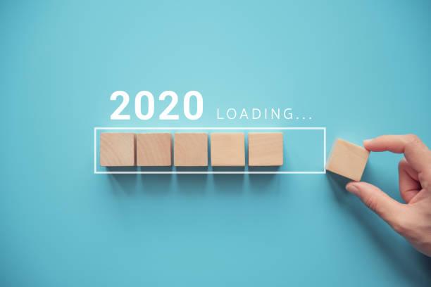 loading new year 2020 with hand putting wood cube in progress bar. - caricare attività foto e immagini stock
