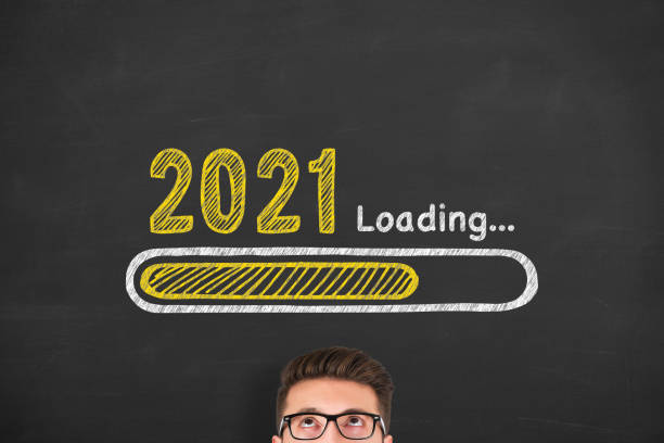 Loading New Year 2021 over Human Head on Blackboard Background stock photo