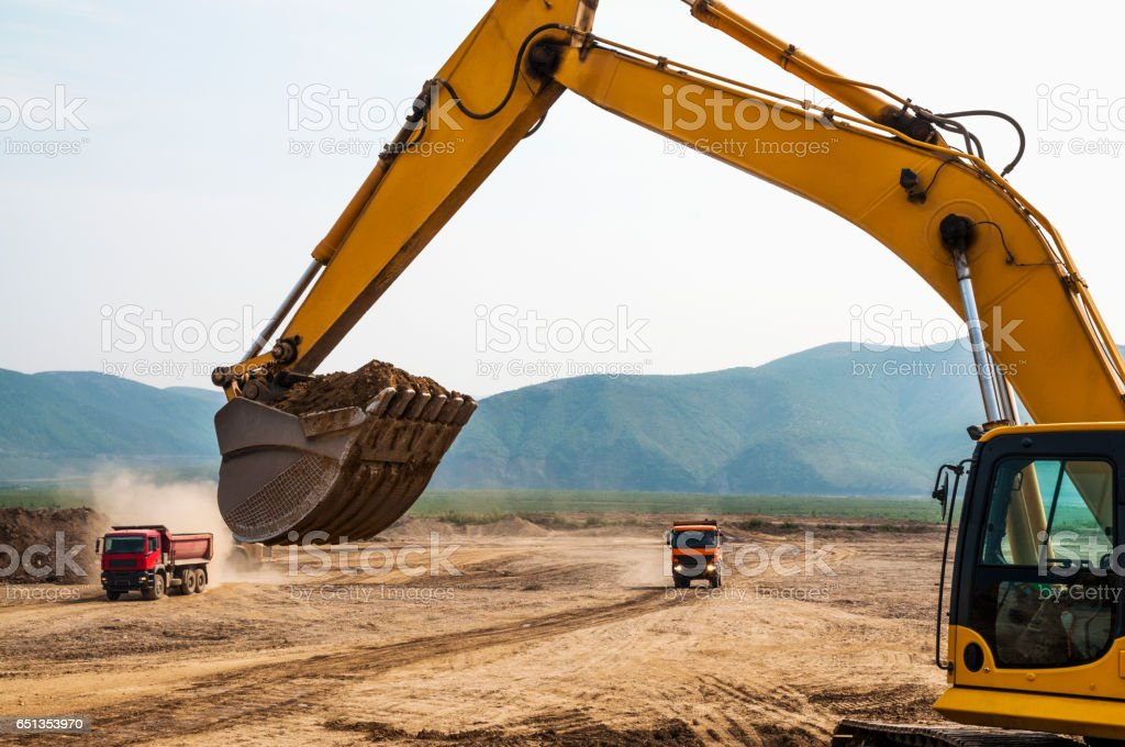 Loading of land ground in trucks using excavator stock photo