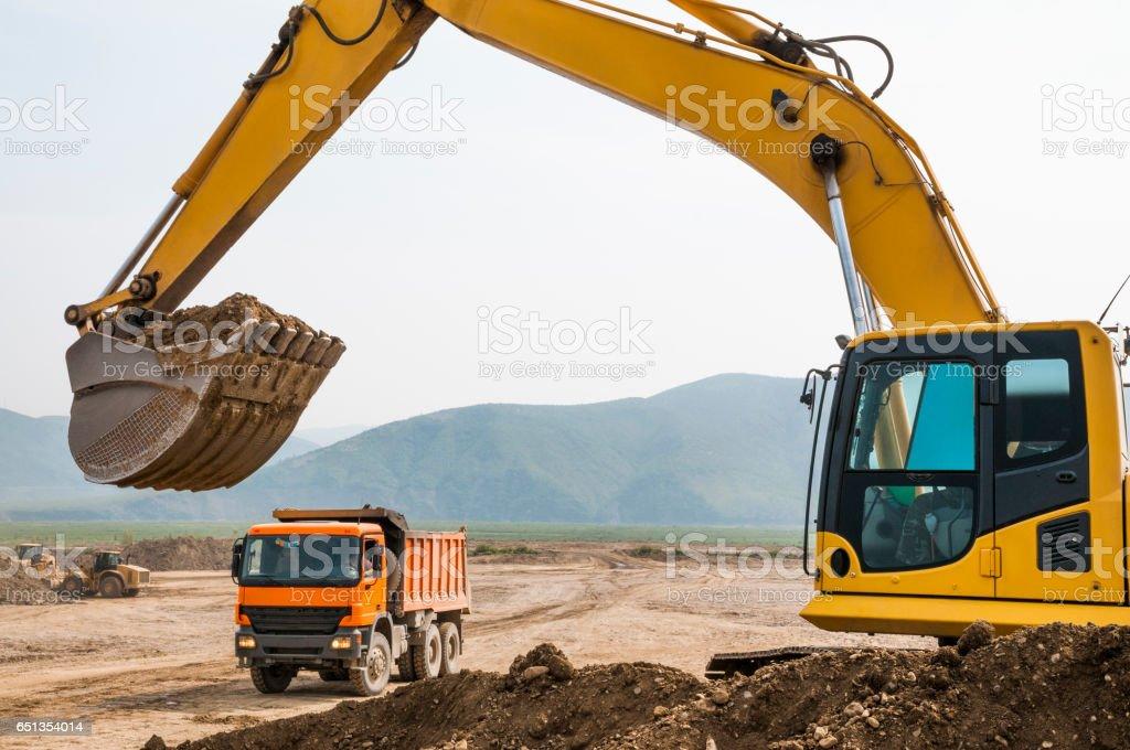 Loading of land ground in trucks using excavator stock photo