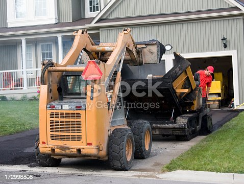 Construction workers loading paving machine with asphalt and paving driveway