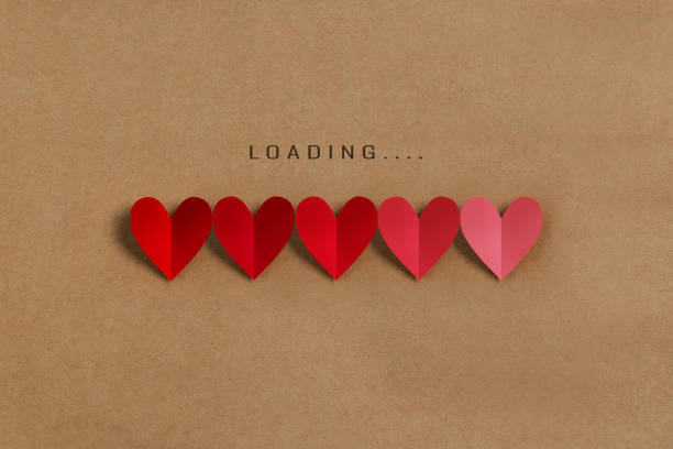 Loading progress bar with red and pink hearts on brown paper background. stock photo