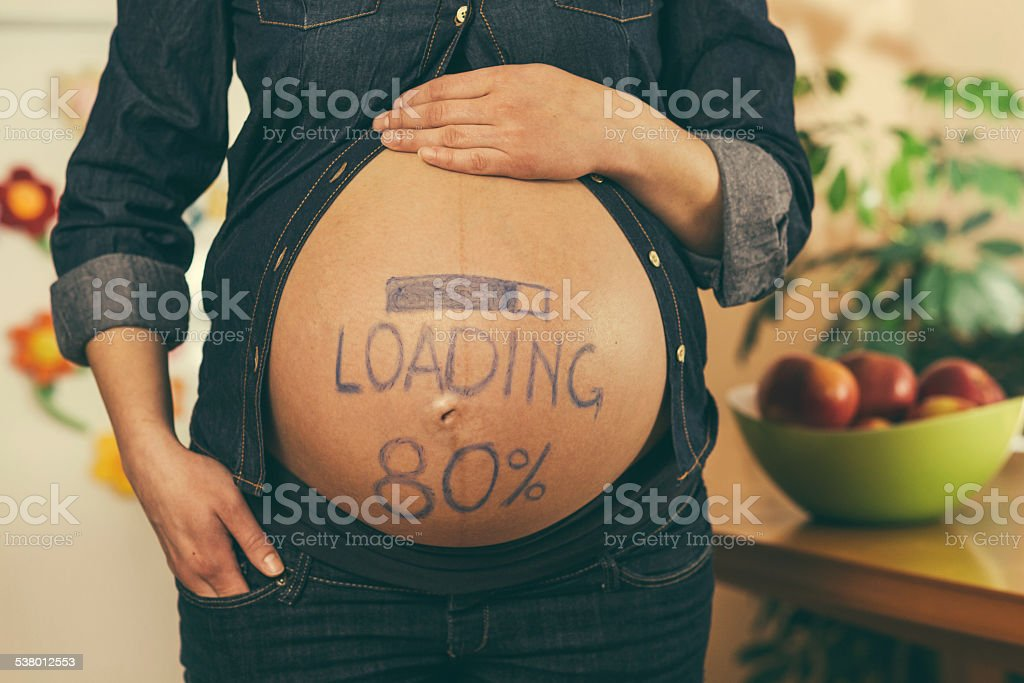 Loading sign on pregnant woman's tummy stock photo
