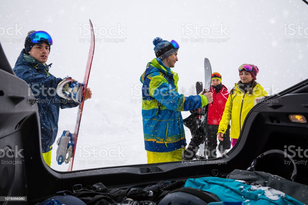 Loading the car after a skiing day in mountain - Snowboarder in the Alps - Group of friends having fun in a winter vacation stock photo